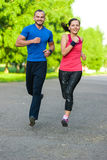 Runners training outdoors working out. City running couple jogging outside. Royalty Free Stock Photos