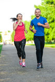 Runners training outdoors working out. City running couple jogging outside. City sport training in green park Royalty Free Stock Photo