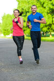 Runners training outdoors working out. City running couple jogging outside. City sport training in green park Stock Photography