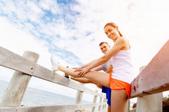 Runners. Young couple exercising and stertching on beach Stock Photos