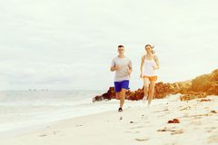 Runners. Young couple running on beach. Together Stock Images