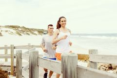 Runners. Young couple running on beach. Together Royalty Free Stock Photo