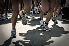 Runnig race. Photo of a running race showing only feet and legs.  Filted dark Stock Photos