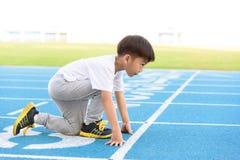 Runnin del ragazzo sulla pista blu Immagini Stock