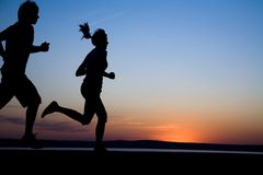 Running. The man and the woman run together on a sunset on lake coast Royalty Free Stock Photo