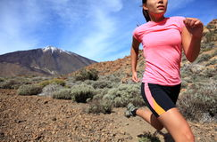 Running. Woman Cross country trail runner  on the mountain / volcano Teide on Tenerife. Beautiful mixed chinese asian / caucasian female model Stock Image
