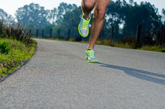 Running. Sport shoes outdoors in action on country road. Male shoes on young man training. Slight motion blur, focus on back  shoe Royalty Free Stock Images