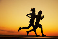 Running. Young couple: men and women run together on a sunset on lake coast. Silhouette Stock Images