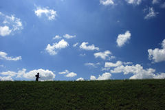 Running. Man against blue sky with clouds stock photography