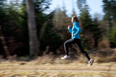 Running. A young woman wearing sports gear running through the woods at a fast pace Stock Images