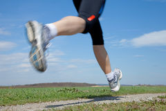 Running. Outdoor closeup shot of a male runner running at a fast pace Royalty Free Stock Photo