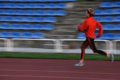 Running. Woman in the orange tracksuit running on the running track Royalty Free Stock Photos