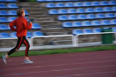 Running. Woman in the orange tracksuit running on the running track Stock Photography