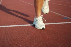 Running. Womans legs -running on the track royalty free stock photography