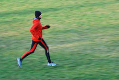 Running. Woman in the orange tracksuit running in cold condition Royalty Free Stock Image
