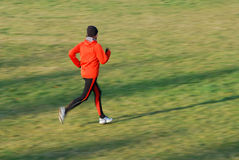 Running. Woman in the orange tracksuit running in cold condition stock photos
