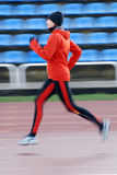 Running. Woman in the orange tracksuit running on the running track Royalty Free Stock Image