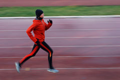 Running. Woman in the orange tracksuit running on the running track royalty free stock photography