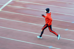 Running. Woman in the orange tracksuit running on the running track Stock Photo