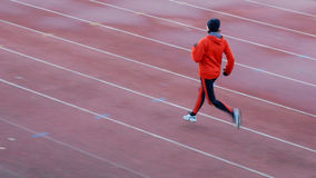 Running. Woman in the orange tracksuit running on the running track Stock Photos