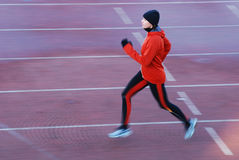 Running. Woman in the orange tracksuit running on the running track Royalty Free Stock Photo