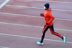 Running. Woman in the orange tracksuit running on the running track Stock Images
