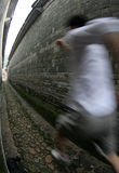Running. A man running in a narrow chinese lane, through grey blocks Stock Images