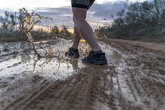 Running across the puddles, at sunset in shorts. stock photos