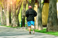 Running. Active elderly man runs cross in the park.  royalty free stock image
