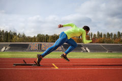 Running african man at stadium. Afro-American man running around the stadium. Young sprinter on the track for jogging Royalty Free Stock Image