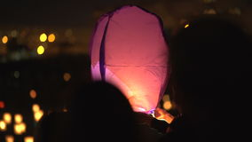 Running the air lantern into the sky. Romantic. Red air flashlight. Sky lantern flying in night sky. Happy defocused people. Running the air lantern into the stock footage