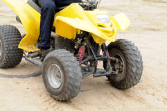 The running all terrain vehicle. A yellow all terrain vehicle ruuning on the sand beach Royalty Free Stock Images