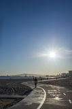Running Along The Road Beside Seashore In Morning. Shots of Woman On the Back Running Along The Road Beside Seashore In Morning, Longbeach Royalty Free Stock Image