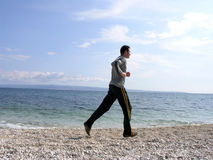 Running Along the Shore. Young man is running along the shore in a sunny day .Space for copy royalty free stock images