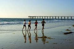 Running along the surf. Four women running along the waters edge Royalty Free Stock Photos