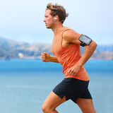Running app on smartphone - male runner. Running app on smartphone. Male runner listening to music jogging with armband for smart phone. Fit man fitness model Stock Image