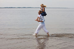 Running around with dad. Child sitting on her dad's shoulders who is running around in the water Stock Images