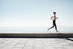 Running asian woman. Female runner training outdoors seaside Stock Images