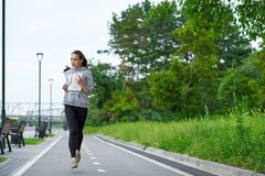 Running asian woman on the waterfront. Morning jogging. The athlete trains stock photos
