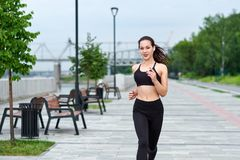 Running asian woman on the waterfront. Morning jogging. The athlete trains royalty free stock photos