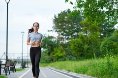 Running asian woman on the waterfront. Morning jogging. The athlete trains royalty free stock image