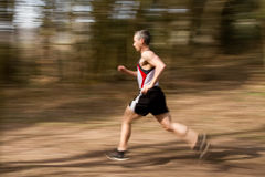 Running athlet. Athlet jogging through the forest Stock Photo