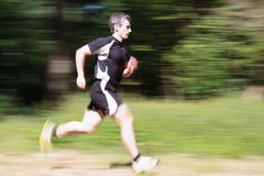 Running athlete. Athlete running in the woods, shot from the side Stock Images