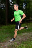 Running athlete. An athlete running through the forest Royalty Free Stock Image