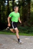 Running athlete. An athlete running through the forest Royalty Free Stock Images