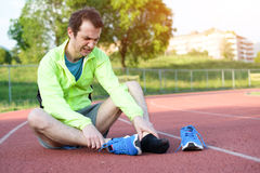 Running athlete feeling pain because of injured ankle Royalty Free Stock Photography