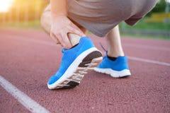 Running athlete feeling pain because of injured ankle. Running athlete feeling pain after an ankle injury Royalty Free Stock Photos