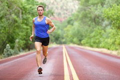 Running athlete man. Male runner sprinting during outdoors training for marathon run. Athletic fit young sport fitness model in his twenties in full body Stock Photos