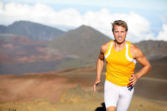Running athlete - man runner sprinting fast. Male sport fitness model training a sprint in amazing nature landscape outdoors at speed wearing sporty runners Royalty Free Stock Photos
