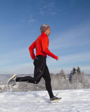 Running athlete in the snow. Athlete running in the snow Royalty Free Stock Photo